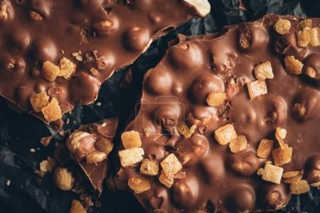 Photo for Top view of milk chocolate with nuts pieces and caramel on crumpled paper - Royalty Free Image