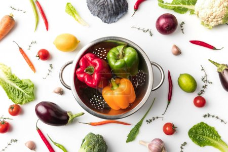 Photo for Top view of colander with colored bell peppers among uncooked vegetables isolated on white - Royalty Free Image