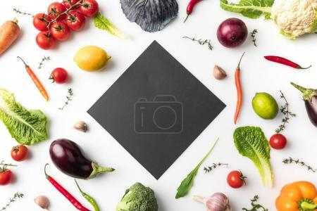Photo for Top view of black board among uncooked vegetables isolated on white - Royalty Free Image