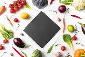 black board among uncooked vegetables