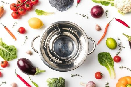 colander among uncooked vegetables