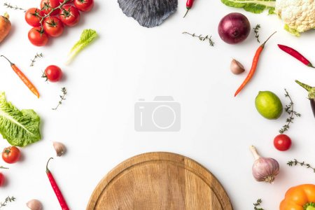 Photo for Top view of wooden board and unprocessed vegetables isolated on white - Royalty Free Image