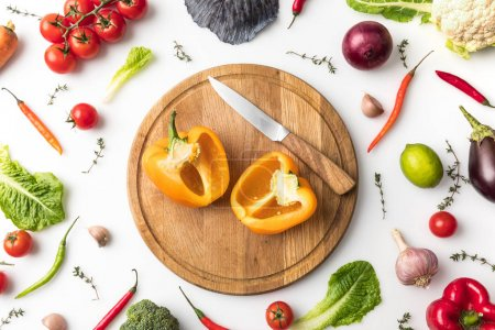 Photo for Top view of cut bell pepper and knife on wooden board isolated on white - Royalty Free Image
