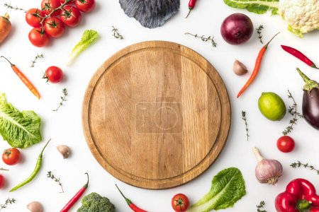 Top view of wooden board among vegetables isolated...