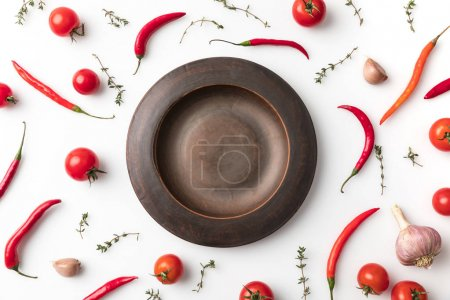 Photo for Top view of black plate among chili peppers and tomatoes isolated on white - Royalty Free Image