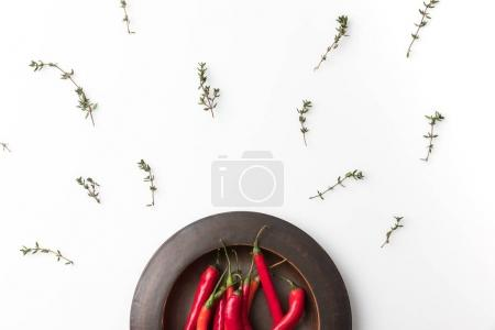 Photo for Top view of red chili peppers on black plate and twigs of thyme isolated on white - Royalty Free Image