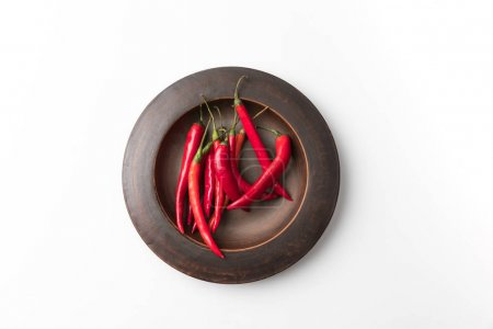 Photo for Top view of red chili peppers on black plate isolated on white - Royalty Free Image