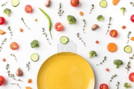 Foto de Vista superior de la placa amarilla de sobre mesa con cortadas verduras aislados en blanco - Imagen libre de derechos
