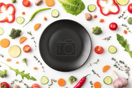 Photo for Top view of black plate in circle of cut vegetables isolated on white - Royalty Free Image