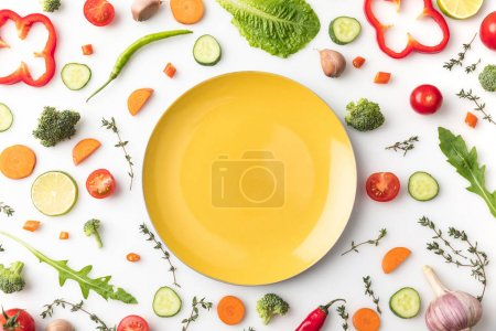 Photo for Top view of yellow plate on table with vegetables isolated on white - Royalty Free Image