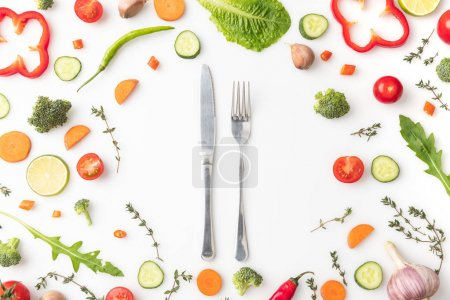 Photo for Top view of knife and fork in circle of cut vegetables isolated on white - Royalty Free Image