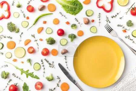Photo pour Vue de dessus de plaque avec fourchette et couteau et légumes sur une table isolée sur blanc - image libre de droit