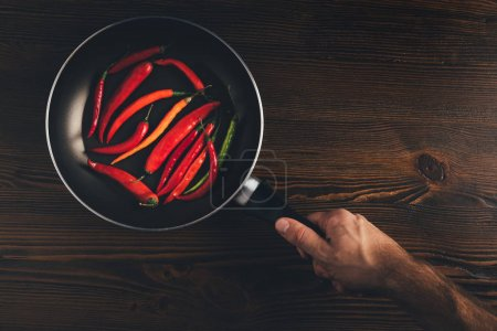 man holding pan with chili peppers