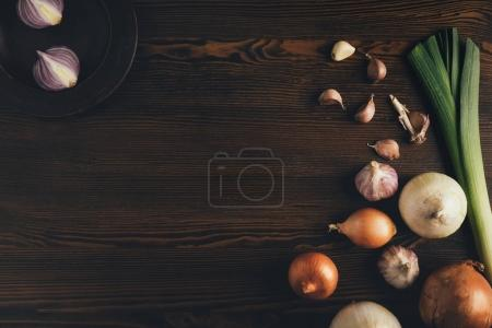 Photo for Top view of onion and garlic on a brown table - Royalty Free Image