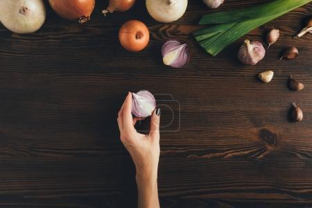 woman holding half of onion