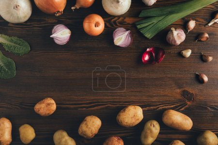 Photo for Top view of potatoes, onion and garlic on a table - Royalty Free Image