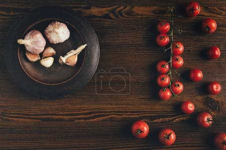 Photo for Top view of plate with garlic and cherry tomatoes on a table - Royalty Free Image
