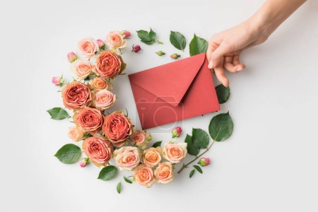 Photo for Hand holding envelope surrounded by beautiful pink flowers isolated on white - Royalty Free Image