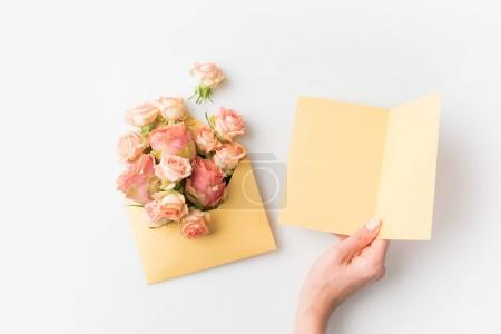 Photo for Hand holding blank paper beside pink flowers in envelope isolated on white - Royalty Free Image