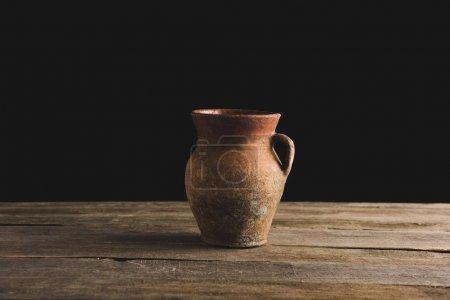 Photo pour Vue rapprochée d'une vieille cruche rustique sur un plateau en bois - image libre de droit