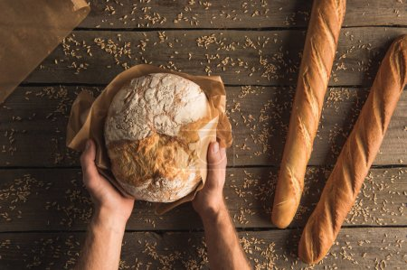 loaf of bread in hands and baguettes