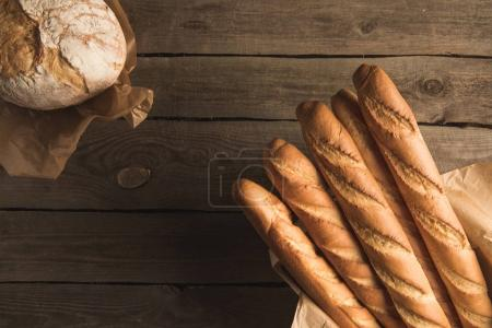 Photo for Top view of fresh baguettes and wholegrain bread on wooden table - Royalty Free Image