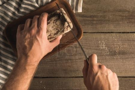 hands cutting loaf of bread