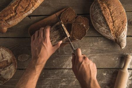 person cutting loaf of bread