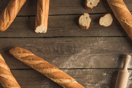 Photo for Top view of fresh whole and sliced baguettes on wooden table - Royalty Free Image