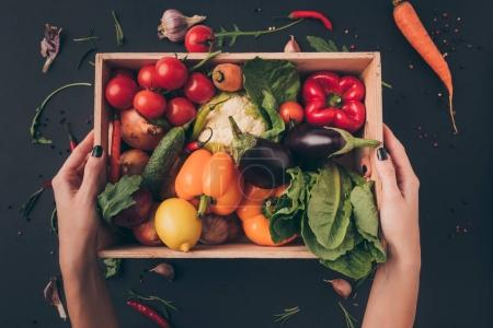 Photo for Cropped image of woman holding wooden box with vegetables above gray table - Royalty Free Image