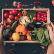 Cropped image of woman holding wooden box with veg...