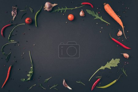 top view of arugula, carrot and chili peppers on gray surface