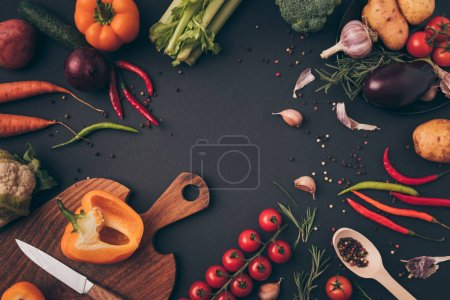 Photo for Top view of knife and cutting board with vegetables on gray table - Royalty Free Image
