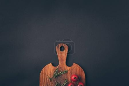 top view of cherry tomatoes and fennel on a wooden board