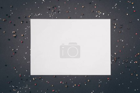 top view of white sheet of paper among scattered pepper on gray table