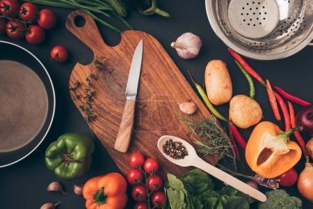 Photo pour Vue de dessus du couteau et la planche de bois entre les légumes sur la surface grise - image libre de droit