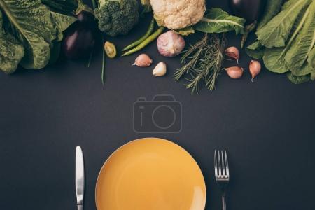 Photo pour Vue de dessus du couteau, fourchette et plaque avec des légumes sur une surface grise - image libre de droit