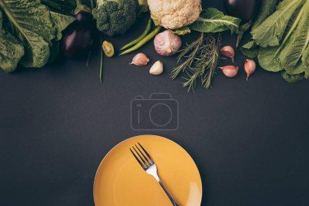 Photo pour Vue de dessus de fourche sur la plaque et les légumes sur la table gris - image libre de droit