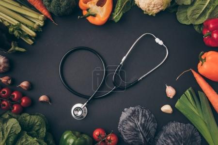 top view of stethoscope among vegetables on gray table