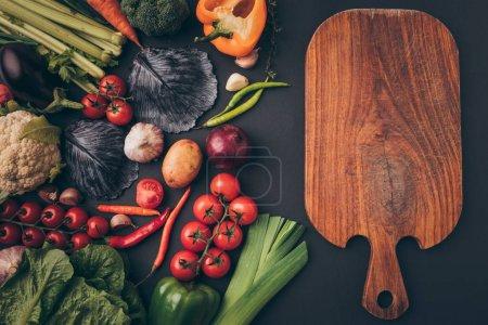 Foto de Vista superior de verduras maduras y tablero de madera en la superficie gris - Imagen libre de derechos