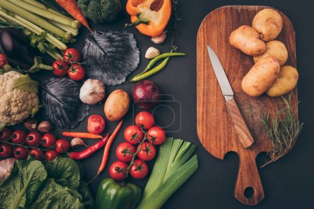 Photo for Top view of ripe vegetables and wooden board on gray table - Royalty Free Image