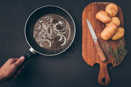 cropped image of man putting frying pan on gray table