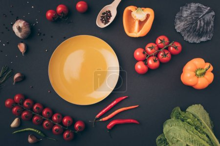 top view of bell peppers and cherry tomatoes with yellow plate on gray table