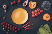 """Постер, картина, фотообои """"вид сверху перца и помидоров черри с желтая тарелку на серый стол"""""""