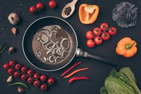 Photo for Top view of frying pan with onion among vegetables on gray table - Royalty Free Image