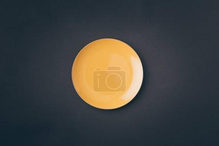 Photo for Top view of yellow plate on gray table - Royalty Free Image
