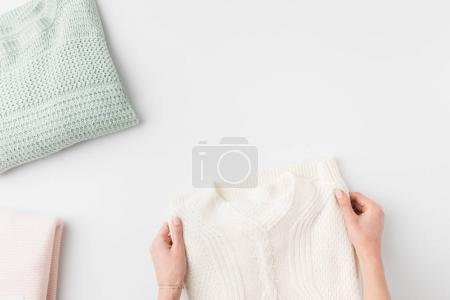 hands with stylish knitted sweaters