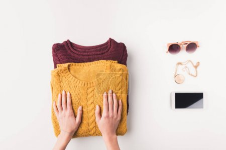 hands with sweaters, accessories and smartphone