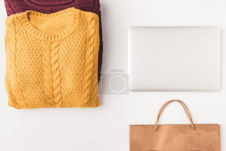sweaters, laptop and shopping bag