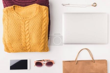 sweaters, laptop, smartphone and shopping bag